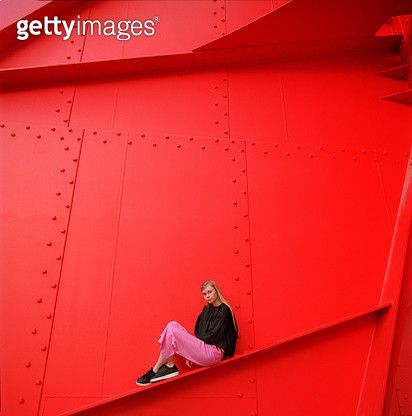 Portrait of young beautiful woman sitting on red color painted metal construction. Shot on medium format film camera - gettyimageskorea