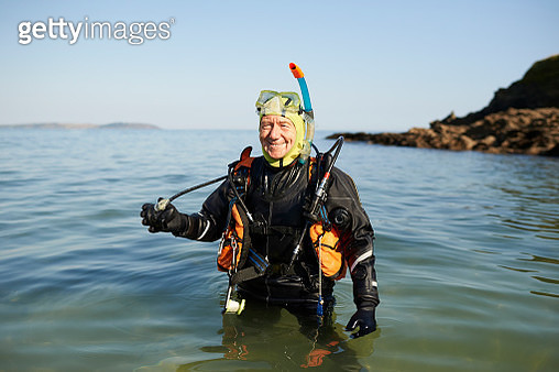 Portrait of senior scuba diver standing in sea with full diving kit. - gettyimageskorea