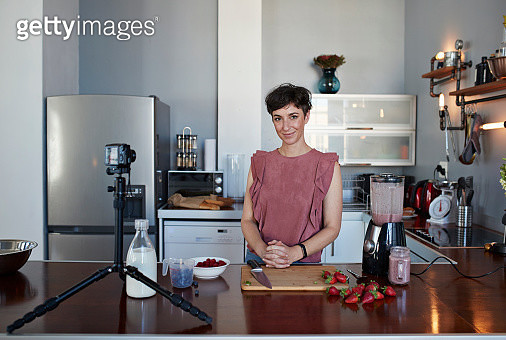 Female food vlogger making video while prepping berries for smoothie - gettyimageskorea