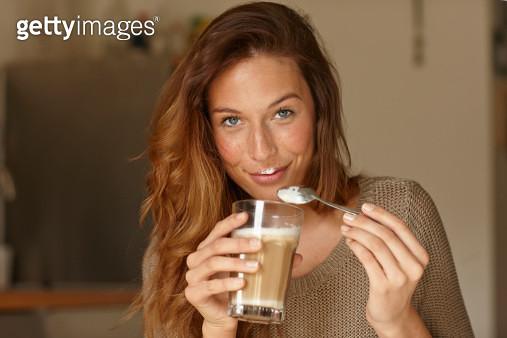 Smiling woman eating coffee foam - gettyimageskorea