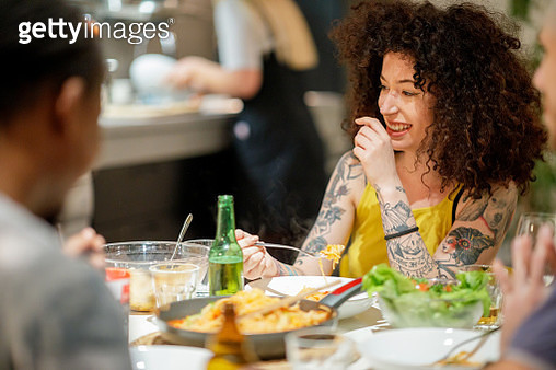 Young woman tsmiling  while dining with roommates italian food at home - gettyimageskorea