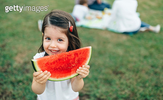 Portrait of smiling girl holding watermelon slice with her family in background - gettyimageskorea
