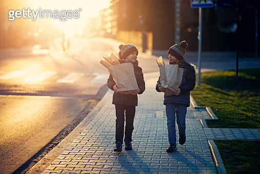 Little boys walking home with shopping bags. - gettyimageskorea