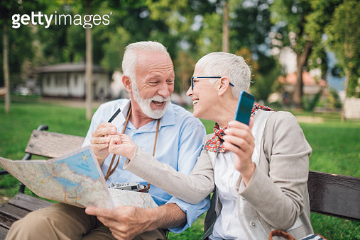 Husband and wife looking at each other while holding a credit card and mobile phone - gettyimageskorea