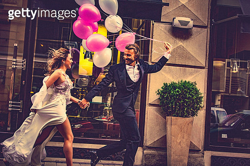 Affectionate bride and groom, holding hands, happily run down the street. Bridegroom carries a bunch of white and pink balloons which flutter behind them. - gettyimageskorea