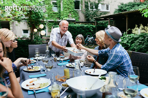 A family sharing food at a large table during a barbecue in a courtyard together. - gettyimageskorea