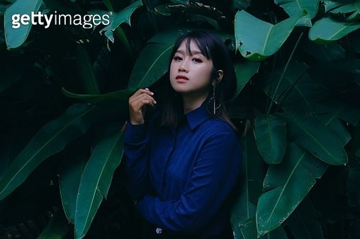 Portrait Of Young Woman Standing Against Leaves - gettyimageskorea