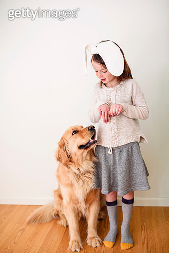 Portrait of a smiling girl wearing bunny ears standing next to her dog - gettyimageskorea