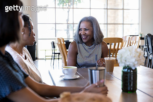 Attractive African American senior woman smiles and listens as her friend discusses something. They are having coffee together in a cafe. - gettyimageskorea