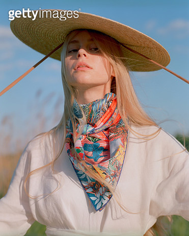 Portrait of young beautiful woman with long blond hair wearing white long dress, colorful silk scarf and wide bordered straw hat standing near lake. - gettyimageskorea