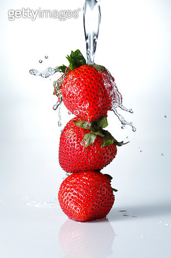 Stack of fresh strawberries with water splash isolated on white background - gettyimageskorea