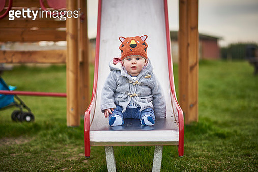 Portrait of a 8 month old British male sat on a slide - gettyimageskorea