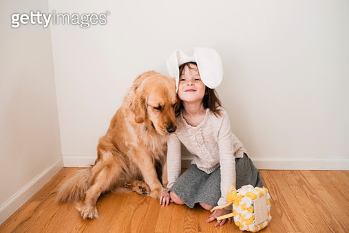 Portrait of a smiling girl wearing bunny ears sitting on the floor with her dog - gettyimageskorea