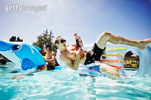 Laughing man playing ukulele floating in outdoor pool on inflatable raft being overturned by swimming friend - gettyimageskorea