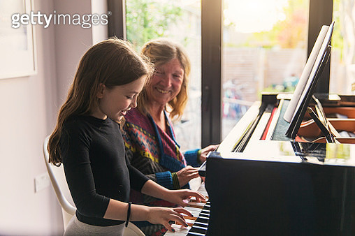Young girl playing the piano with her grandmother - gettyimageskorea