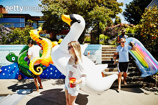 Smiling friends carrying drinks and large inflatable pool toys during party at backyard pool - gettyimageskorea