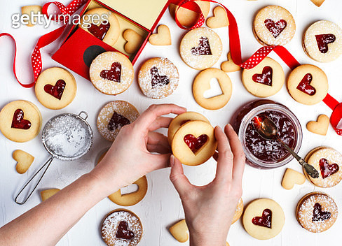 Traditional Linzer cookie with strawberry jam, top view. Female hands making cookies. - gettyimageskorea