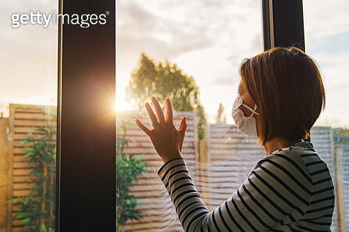 Woman with mask looking through window - gettyimageskorea