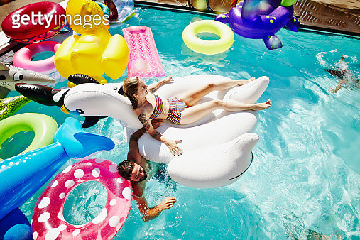 Laughing woman floating on large inflatable pool toy in outdoor pool during pool party with swimming friends and different pool toys in background - gettyimageskorea