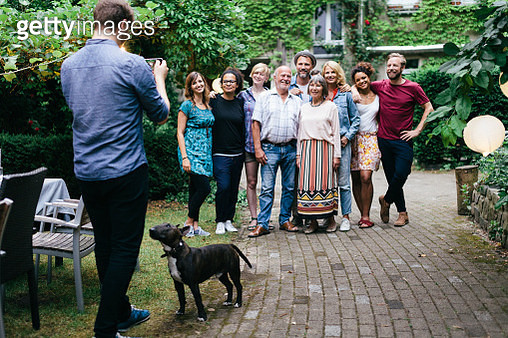 A man taking a photo of his friends and family after a barbecue meal together. - gettyimageskorea