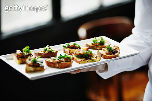 Waitress holding platter of organic appetizers - gettyimageskorea
