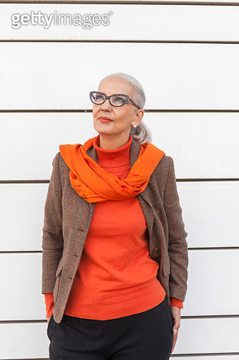 Portrait of fashionable mature woman in front of white wall - gettyimageskorea
