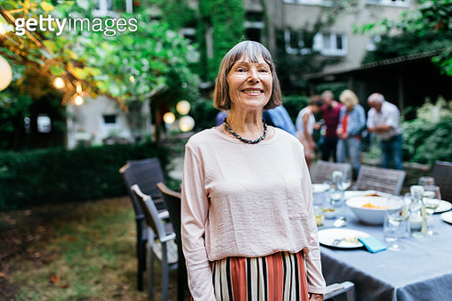 A  portrait of an elderly woman smiling after enjoying a barbecue in a courtyard with her family. - gettyimageskorea