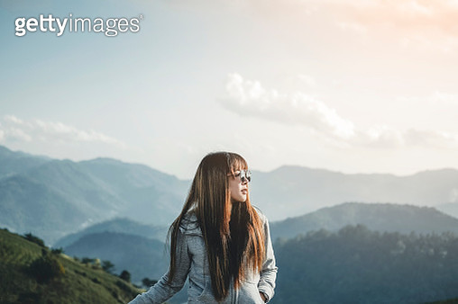 Happy Woman Enjoying Freedom on top of mountain with sunset relaxation concept - gettyimageskorea