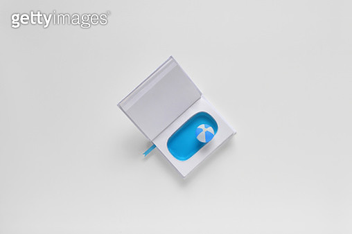 Conceptual papermade swimming pool and beach ball in a book - gettyimageskorea