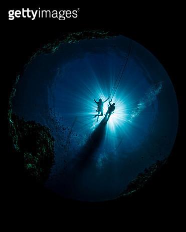 Underwater scene of divers in current - gettyimageskorea