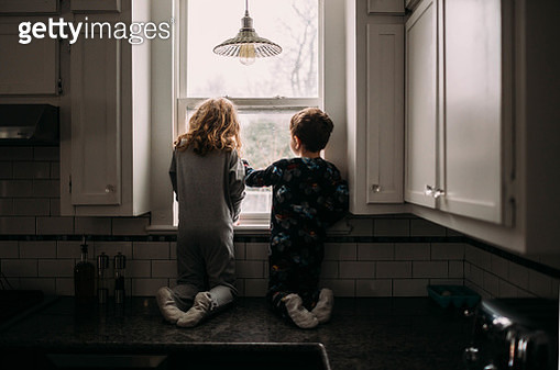 Brother and sister looking outside kitchen window on cloudy day - gettyimageskorea