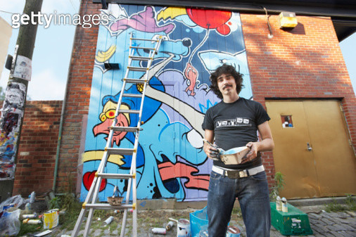 Young man painting mural on wall, portrait - gettyimageskorea