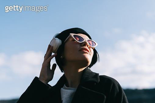 Portrait of young woman listening to music outdoors - gettyimageskorea