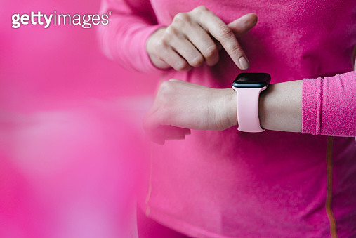 Close-up of woman in pink sportswear adjusting her smartwatch - gettyimageskorea