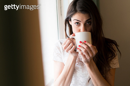 Portrait of woman drinking cup of coffee - gettyimageskorea