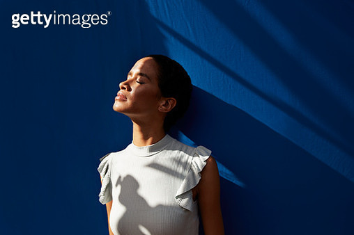 Thoughtful young woman standing against blue wall - gettyimageskorea