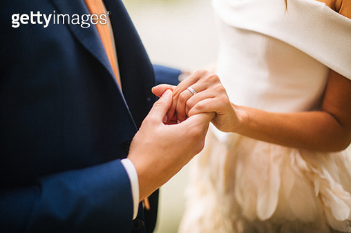 Groom hold brides hand with silver wedding ring - gettyimageskorea