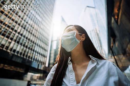 Young Asian businesswoman with protective face mask to protect and prevent from the spread of viruses during the coronavirus health crisis, standing in an energetic and prosperous downtown city street against corporate skyscrapers - gettyimageskorea