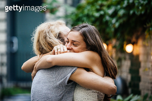 A young couple lovingly embrace each other during a meetup and barbecue with friends. - gettyimageskorea