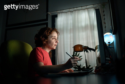 A woman works on her computer at her home office - gettyimageskorea