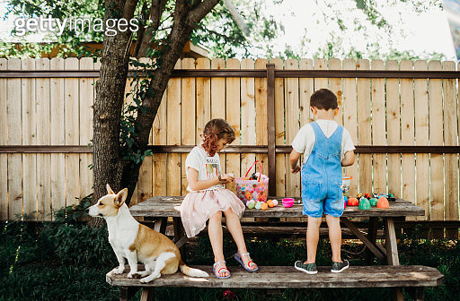 Young brother and sister looking through easter eggs outside - gettyimageskorea