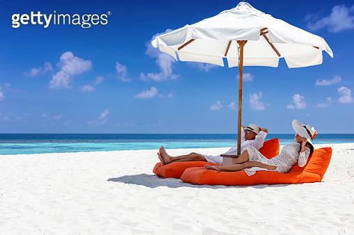 Couple Relaxing On Mattress Under Parasol At Beach - gettyimageskorea