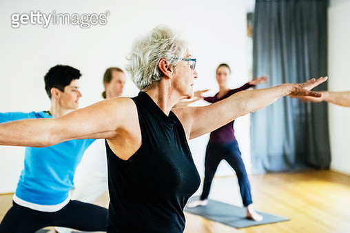A mature woman performing poses and keeping fit in an amateur yoga class. - gettyimageskorea