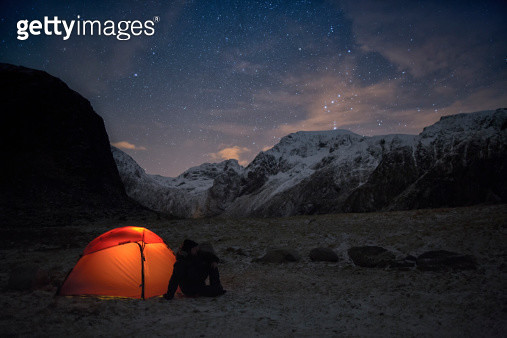 Lonely camper looking at the starry sky in wintertime - gettyimageskorea