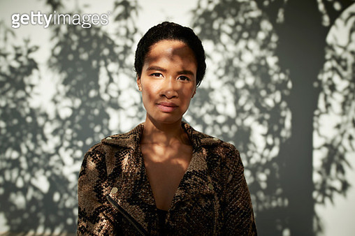 Portrait of woman standing against white wall - gettyimageskorea