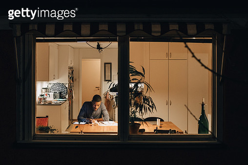 High angle view of boy studying while sitting at home seen through window - gettyimageskorea