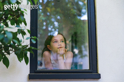 Young girl looking through window - gettyimageskorea