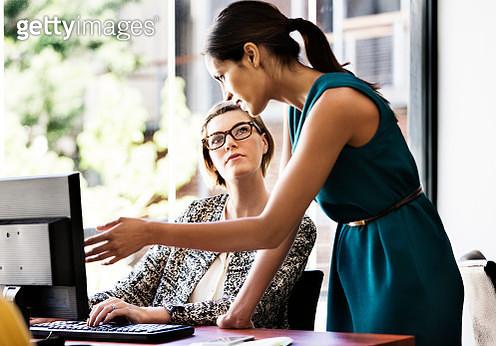 Businesswomen working at computer desk in office - gettyimageskorea