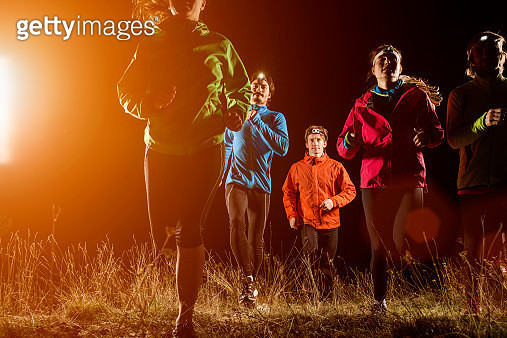 Joggers running on field at night - gettyimageskorea