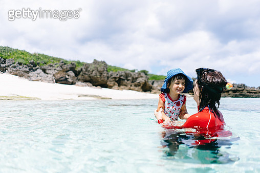 Mother and child playing in clear tropical water, Amami Islands, Japan - gettyimageskorea